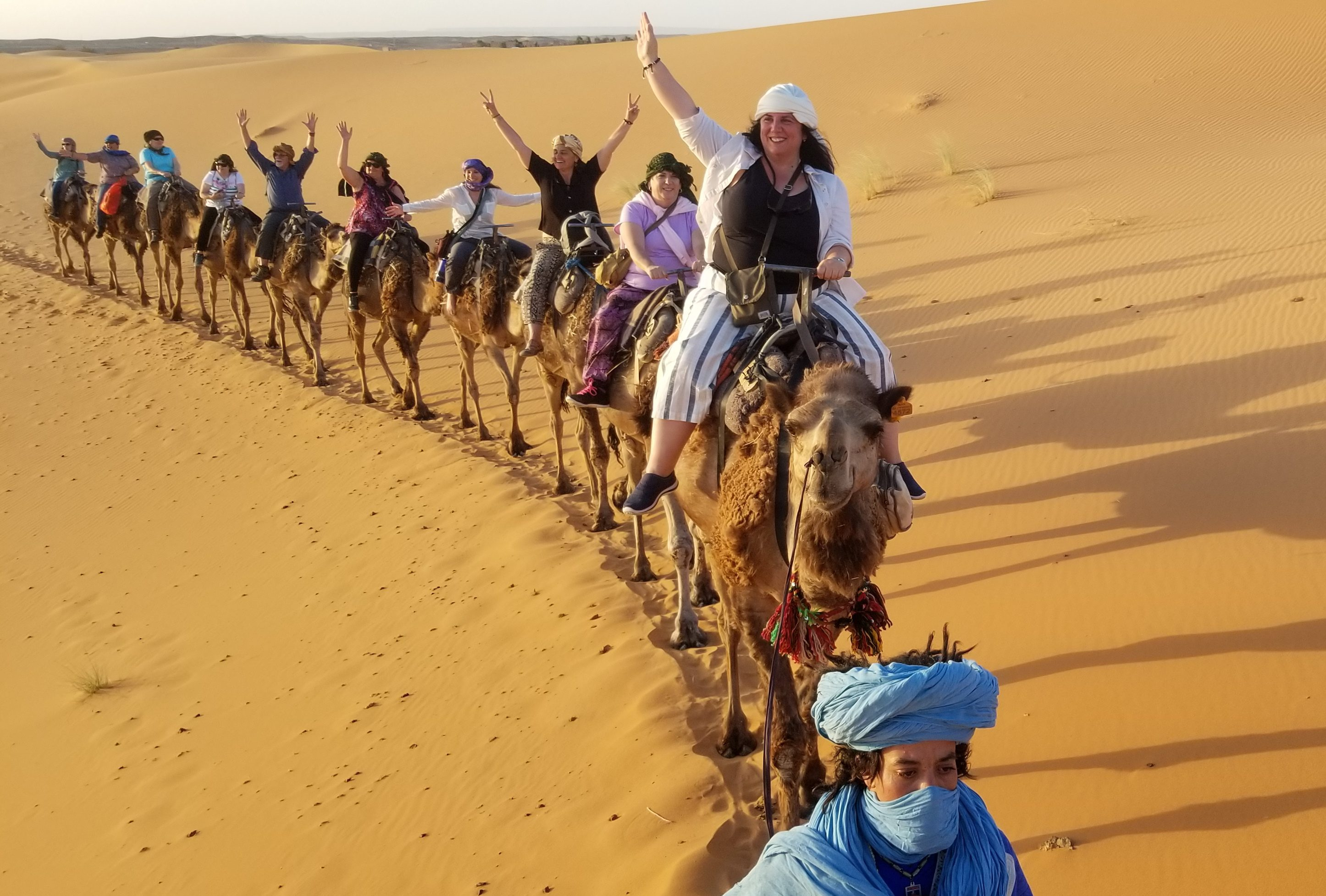 Camel train with travelers cheering