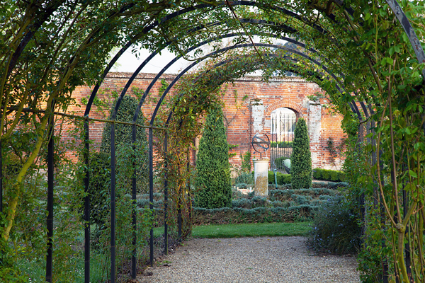 Arbor with greenery and brick estate in the background