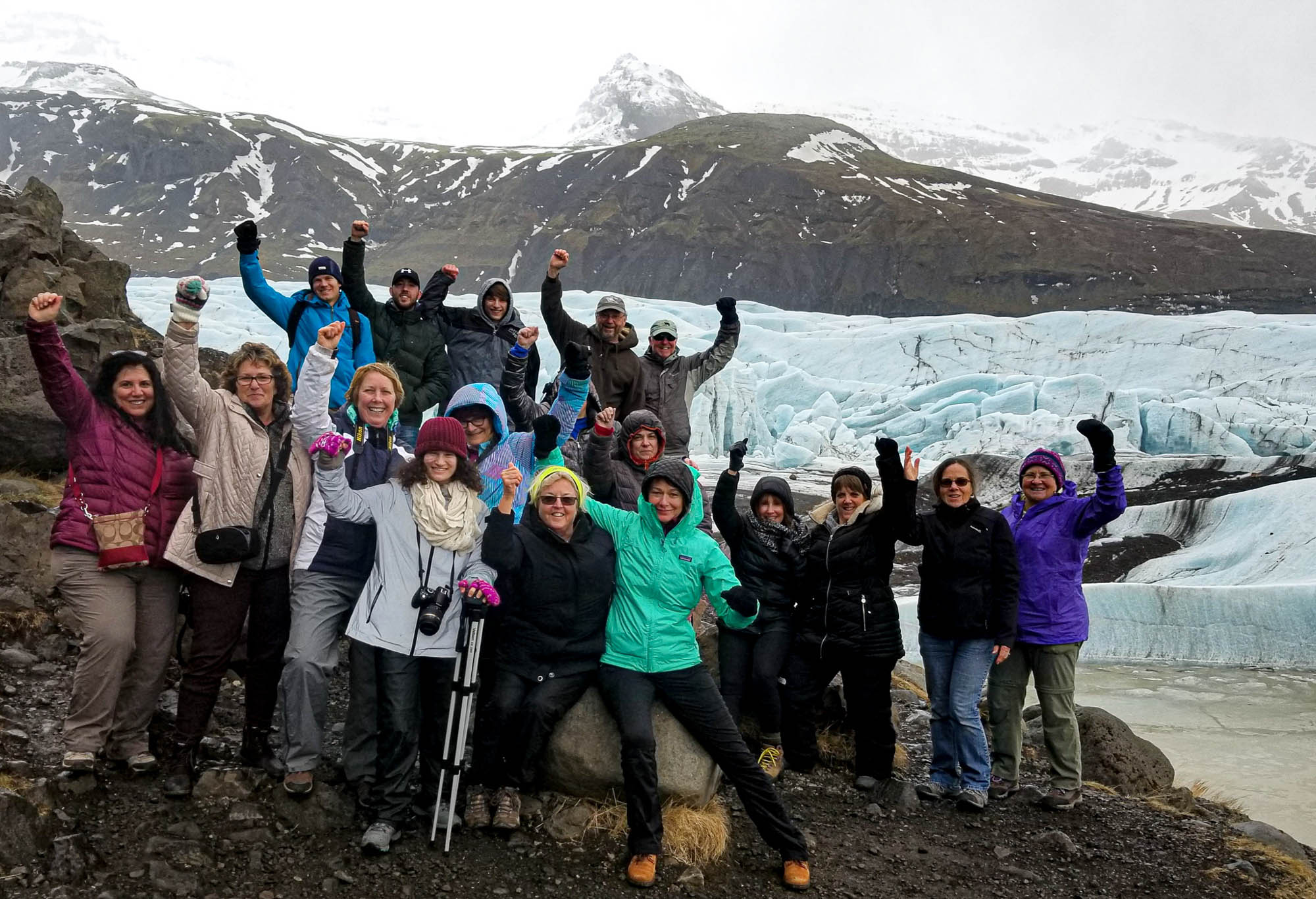 Tour group standing by a glacier in iceland cheering