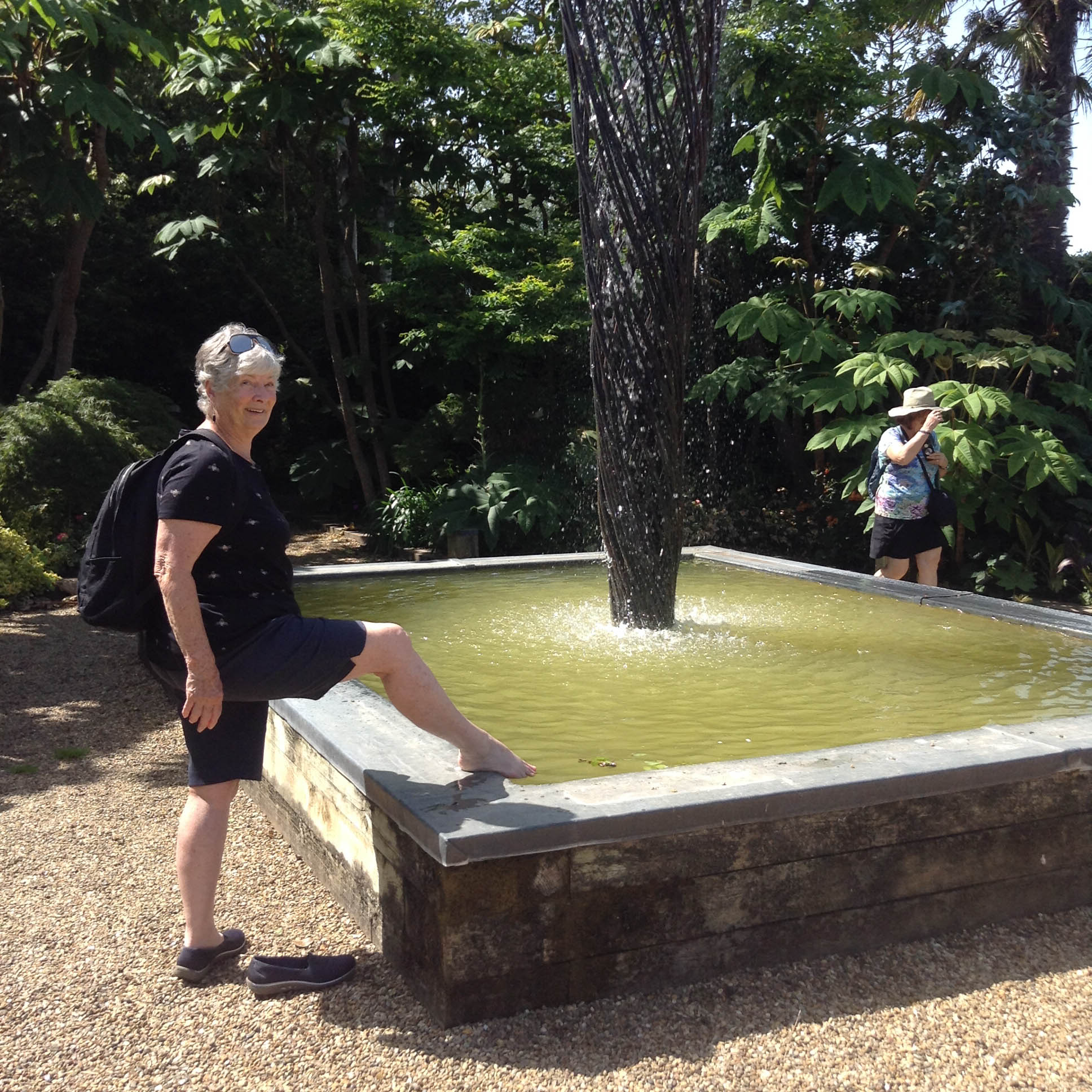 Woman cooling achy feet in a fountain