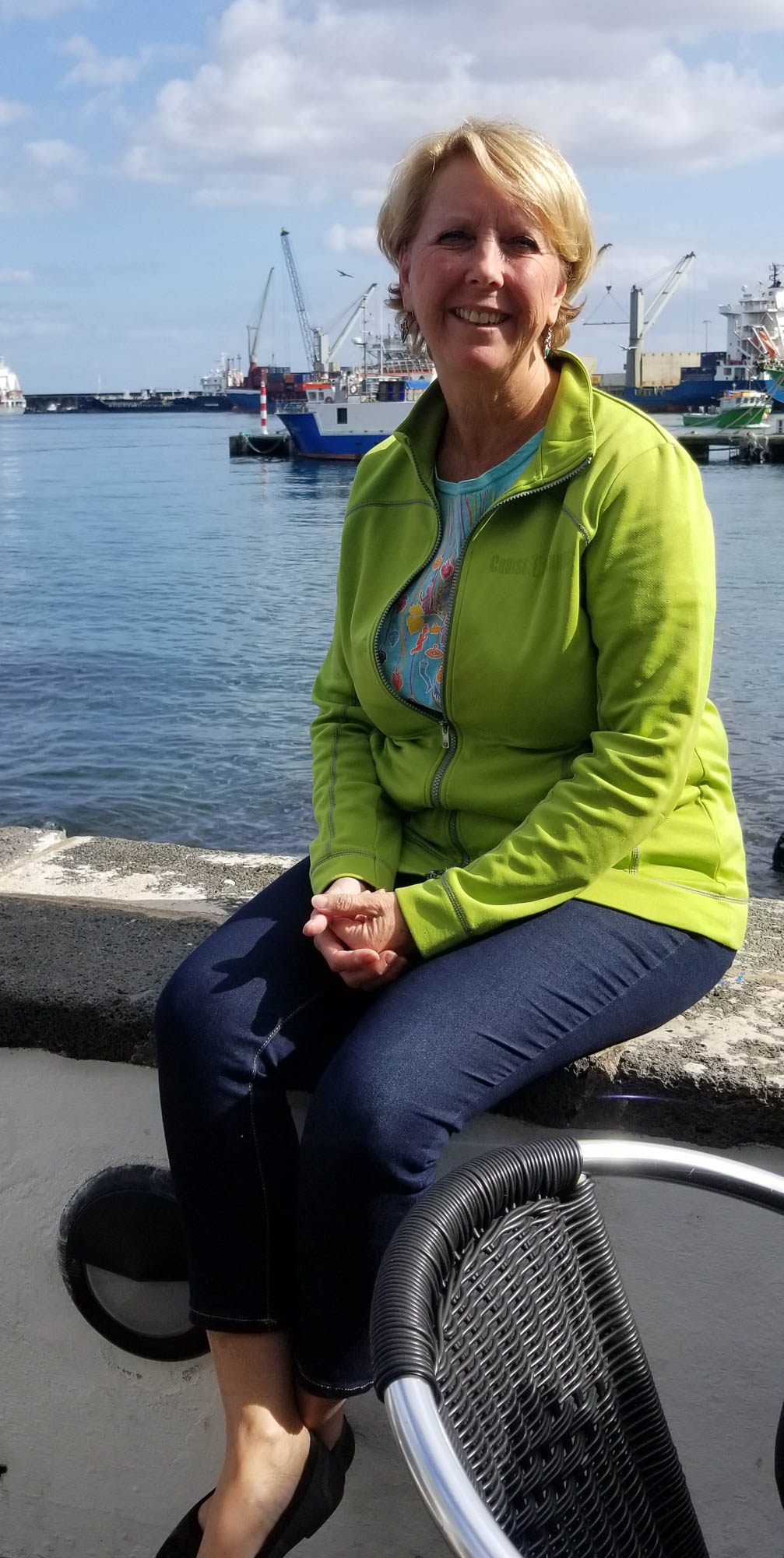 Woman sitting on wall in Sao Miguel, Azores harbor