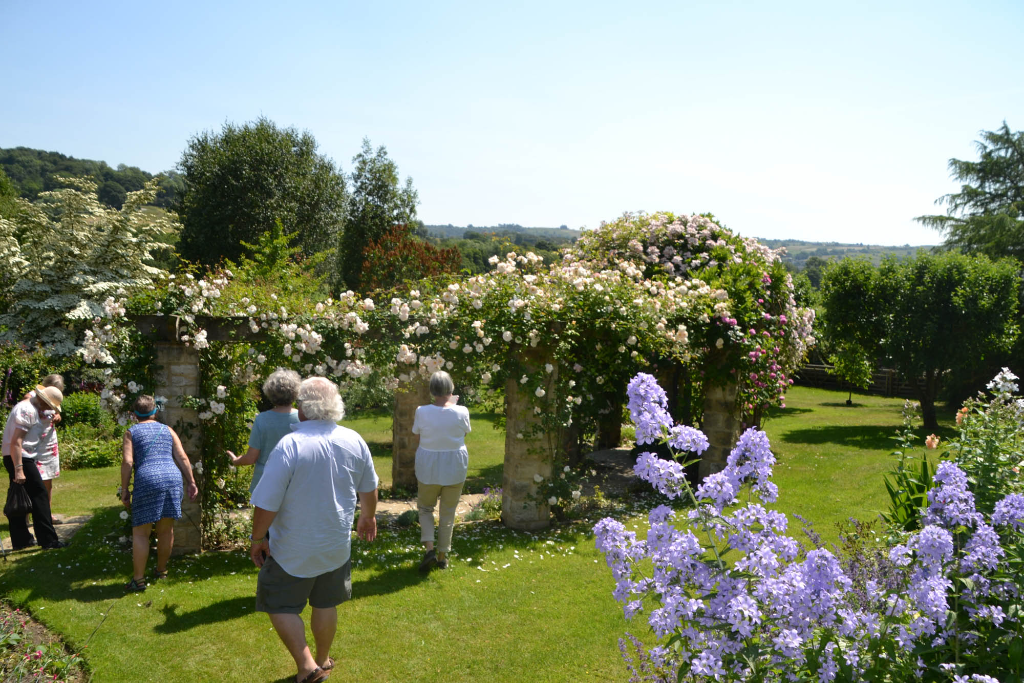 GArden tour group looking at a rose arbor in England