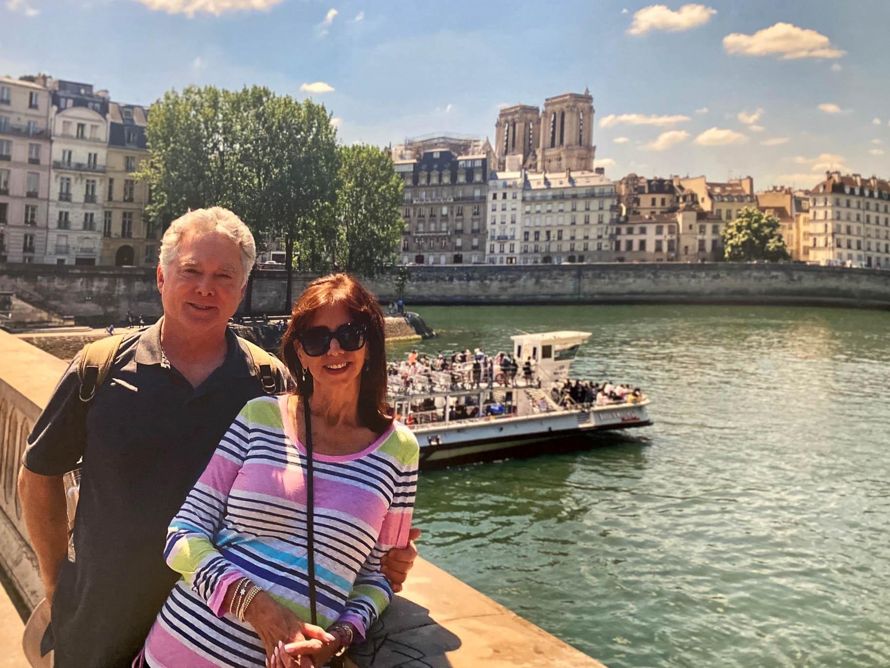 Couple standing on bridge across the Seine in Paris