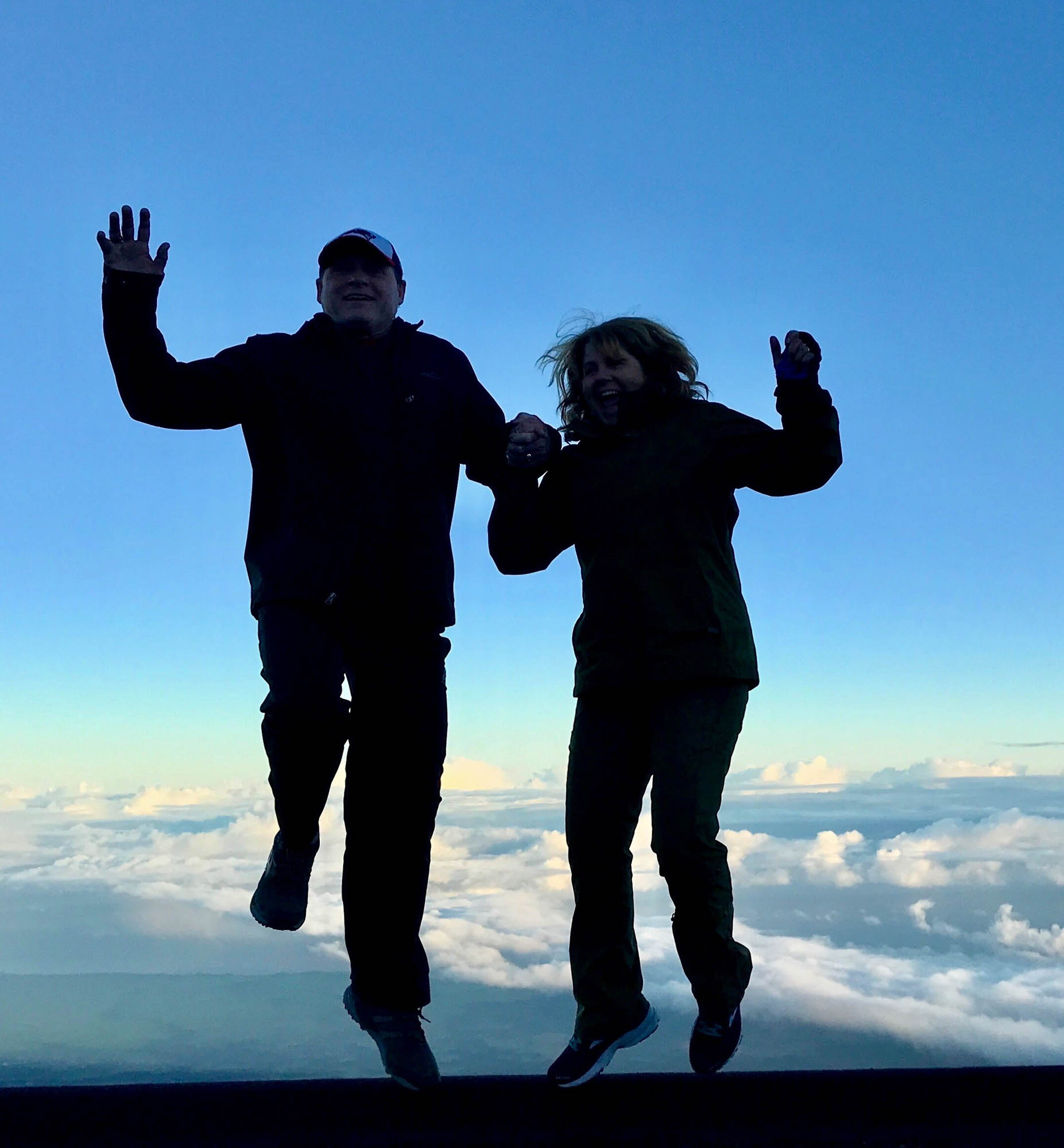 Couple jumping, holding hands, blue sky