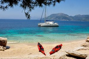 Catamaran anchored off shore with 2 red kayaks on the beach