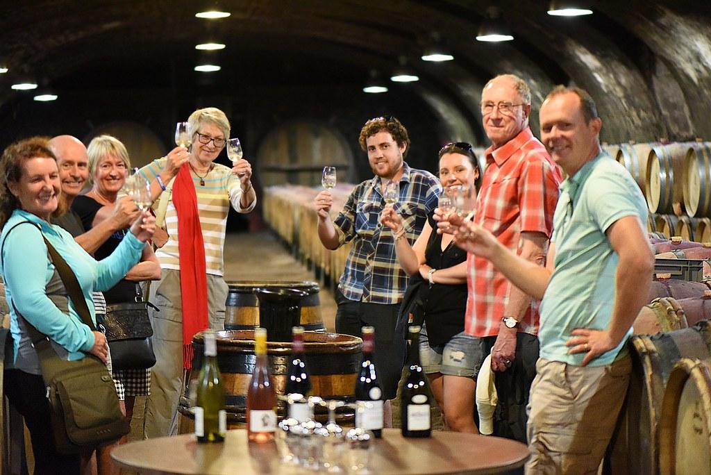 People standing in wine cellar tasting wine