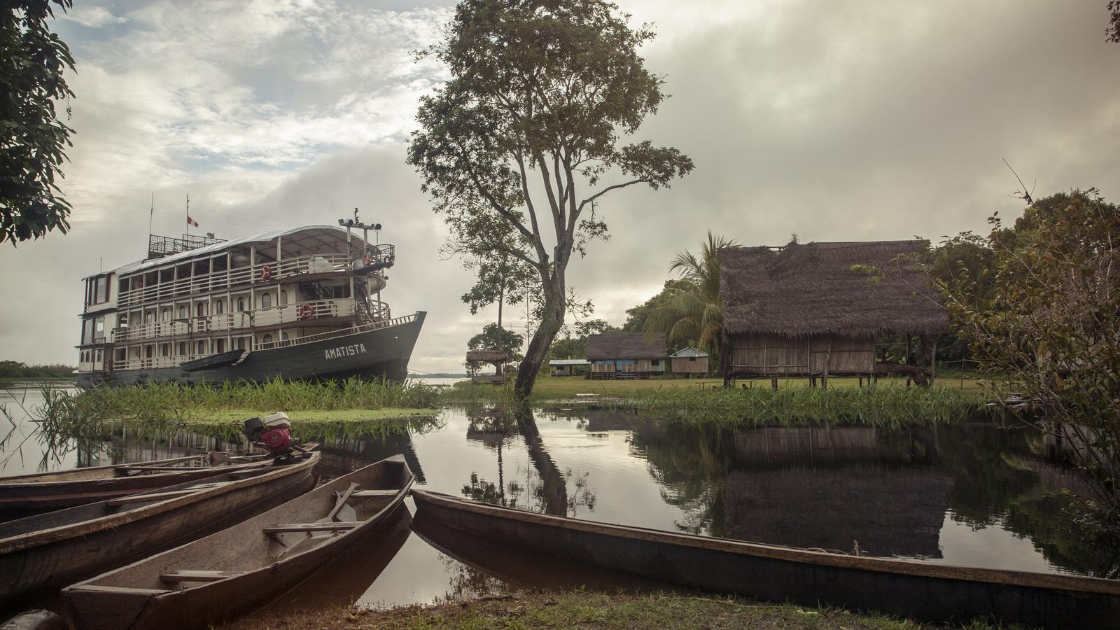 Riverboat on the amazon with 3 skiffs in the forground
