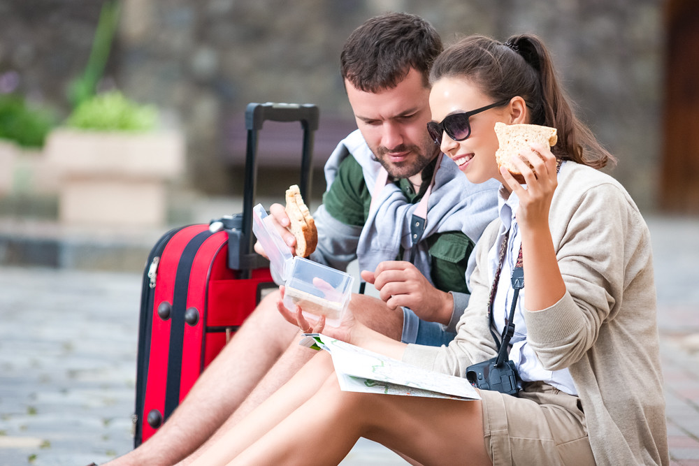 couple looking at map, eating sandwich, with red suitcase