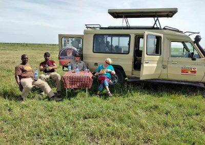 people sitting by their jeep on the serengeti